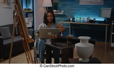 Invalid black person with laptop computer designing artwork in creative space at home. Artistic african american woman in wheelchair working with device seeking inspiration for masterpiece