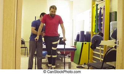 Invalid in orthosis trying to walk with support of two...