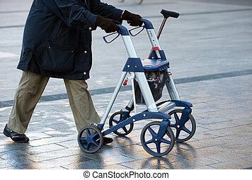 Invalid with walker - An elderly woman walking on the street...
