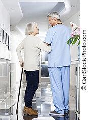 invalide, oude vrouw, vasthouden, stok, terwijl, kijken naar, physiotherap
