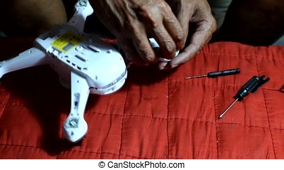 Inventive, resourceful Old man repairing broken quad-copter...