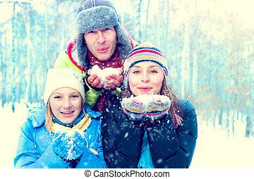 inverno, famiglia, outdoors., felice, gioioso, famiglia, con, capretto, soffiando, neve