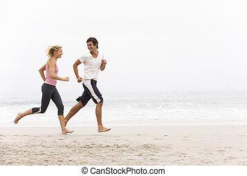 inverno, par, jovem, funcionar ao longo praia