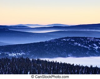 Inverse weather in mountains, shinning fog. Misty valley in...