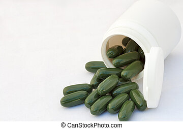 inverted bottle with green capsules against white - inverted...