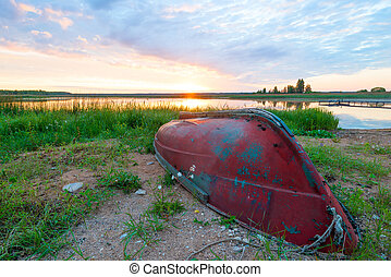 inverted old boat on the shore of the lake at dawn