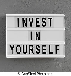 'Invest in yourself' words on a light box on a concrete surface, overhead view. Flat lay, from above, top view.