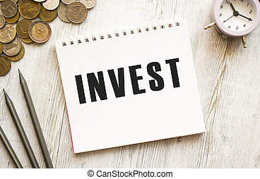 INVEST text on a sheet of notepad. Coins are scattered, pencils on a gray wooden background.