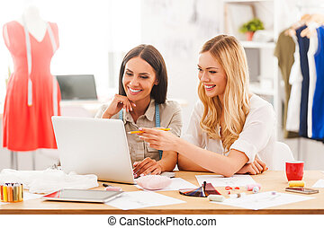 investigar, el, nuevo, moda, trends., dos, alegre, mujeres jóvenes, trabajo junto, mientras, sentado, en, el, escritorio, en, su, moda, taller