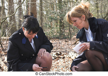 Investigating a crime scene - Two female police officers...