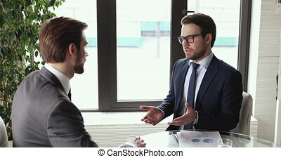Investment adviser consulting handshaking male client investor at meeting making commercial financial deal. Two businessmen wear suits shake hands for future partnership business development concept.