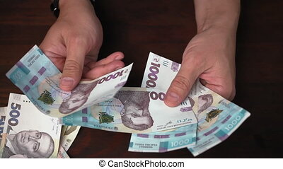 Investment concept. New Ukrainian paper money in male hands. Rich man considering paper notes in denominations of 1000 hryvnias. Prores 422.