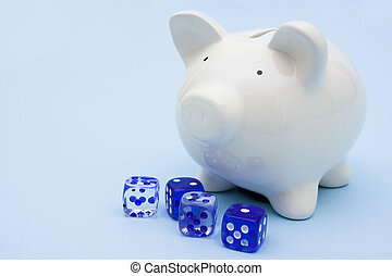 Piggy bank with dice sitting on a blue background, investment gambling