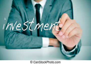 investment - businessman sitting in a desk writing the word...