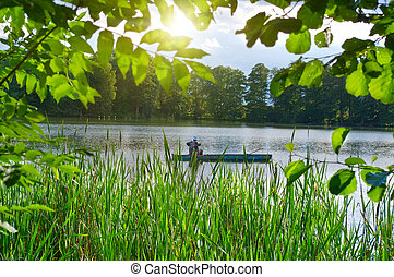 Inveterate fisherman in a boat on the lake. Summer fishing