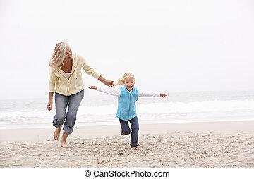 invierno, nieta, abuela, ejecución a lo largo de la playa