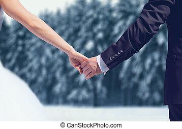 invierno, par wedding, novia y novio, manos de valor en cartera, encima, nevoso, bosque, plano de fondo