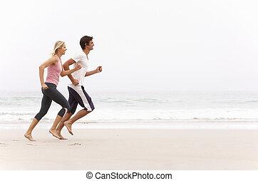 invierno, pareja, joven, ejecución a lo largo de la playa