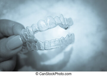 Invisible dental retainer held by womans hand