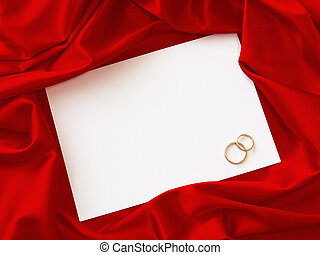 invitation card with two wedding rings and red cloth around