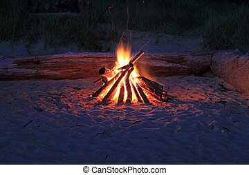 Inviting campfire on the beach is a summer tradition