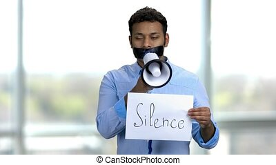 Involuntary silence concept. Young indian man is trying to ...