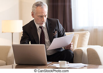 Involved businessman working with papers and sitting in the hotel