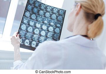 Involved neurosurgeon examining roentgen brain results at...