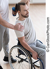 Involved young disabled man exercising in the gym