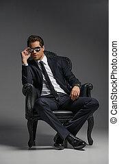 io, sono, uno, boss., fiducioso, giovane, uomini affari, in, occhiali da sole, seduta, su, il, vendemmia, sedia, mentre, isolato, su, grigio