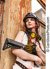 portrait of army girl with rifle in camouflage clothes in urban scene, in hiding