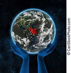 Iran on night planet Earth in hands