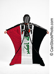 Iraq flag travel. Simulator of free fall. Men in wing suit.