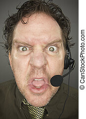 Irate Businessman Wearing a Phone Headset Against a Grey...