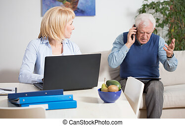 Irate man - Elderly irate man talking phone with the client