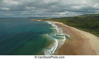 Ireland aerial view: beach ocean bay water crashing. People on shore walk