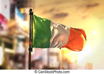 Ireland Flag Against City Blurred Background At Sunrise Backlight