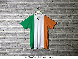 Ireland flag on shirt and hanging on the wall with brick pattern wallpaper.