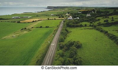 Ireland rural road aerial view: car driving up farmland. Irish green grass meadow, fields and pastures in summer evening. Majestic Irish landscape of countryside roadway. Footage shot in 4K, UHD