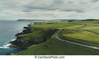 Green fields, meadows aerial: road cars driving on background. Ireland's hills, farmlands, clouds on horizon. Picturesque landscape view of Antrim County, United Kingdom. Footage shot in 4K, UHD
