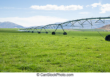 Irigation system, long moveable booms of the water distribution plant stretches across farming fields on Otago, New Zealand.