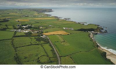 Irish aerial green fields landscape shot: road along meadows. Ireland wide plants and farms