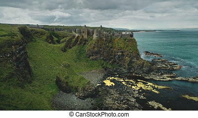 Irish castle cliff shore aerial view: Dunluce on green grass valleys and meadows overlooking ocean bay. Beautiful stones and reefs. Beauty of Northern Ireland's historic ruins. Footage shot in 4K, UHD