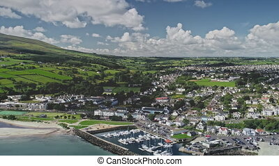 Irish coastal cityscape aerial view of pier Ballycastle, Co Antrim. Yachts, ships on ocean water surface. Houses, cottages with roads, mountain green hills. Majestic bird's-eye footage shot in FullHD