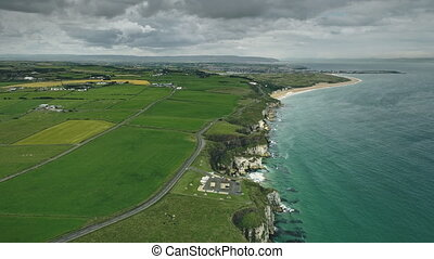 Irish countryside cliff coast aerial panoramic shot: green fields, meadows and ocean bay under cloudy sky. Beautiful landscape and rock coastline of Northern Ireland. Dramatic view footage in 4K, UHD