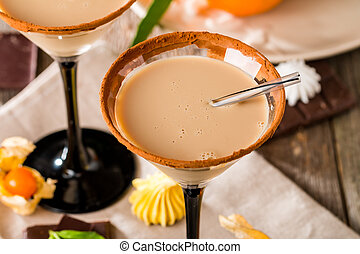 Irish cream liqueur in a glass with cinnamon on wooden ...