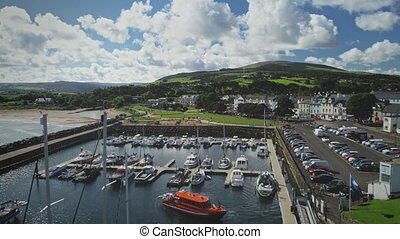 Irish ocean pier town aerial view: port landscape with yachts against mountain top. Epic beauty of harbour Atlantic bay amidst nature of Ireland. Clouds on bright summer day. Footage shot in 4K, UHD