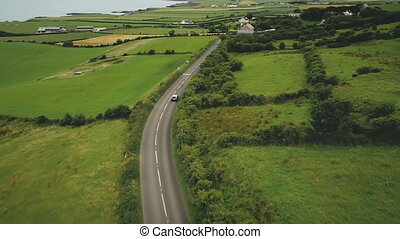 Irish rural road aerial view: green meadows against cottages and hillside farmlands. Picturesque landscape with grain fields in Antrim County, Northern Ireland. Cinematic footage shot in FullHD