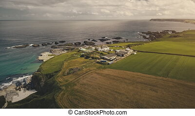 Irish Whiskey Distillery at sun cliff ocean shore aerial. Whisky manufacturing factory with warehouses at fields and farmland. Carrick Island, Antrim county, Northern Ireland, United Kingdom, Europe