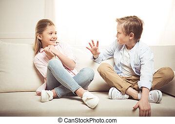 irmã, sentando, sofá, irmão, junto, alegre, falando, enquanto, lar